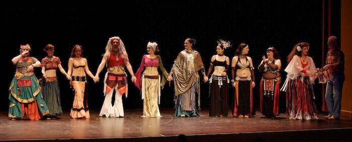 Photo of: Line-up for perfomers at Bloomington Belly Dances - 2007 receiving flowers from Roger Meridith and Margaret Lion during their curtain call.